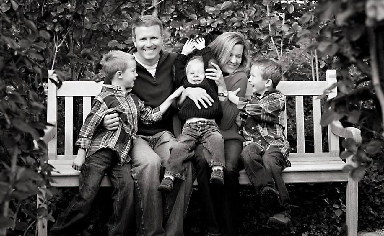family of five on bench laughing and smiling
