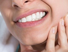 woman gritting teeth with toothache