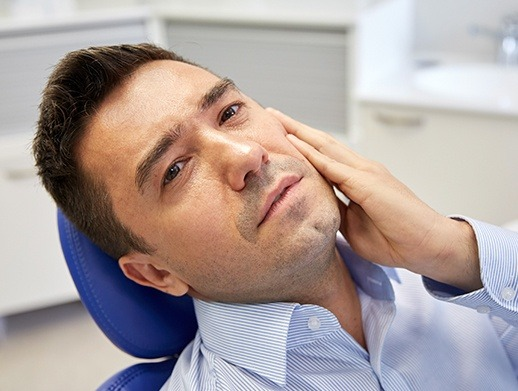 man laying back in pain holding cheek before emergency dentistry