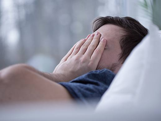man in bed covering face tired in need of sleep apnea therapy