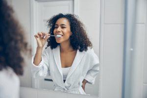 woman brushing her teeth to extend the lifespan of veneers in Skokie