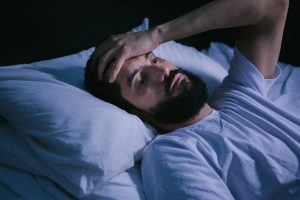 Man awake in bed suffering from sleep apnea in Skokie